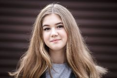 一点美丽的时髦的孩子女孩特写镜头画象有长期流动的头发的对棕色镶边墙壁 免版税库存图片