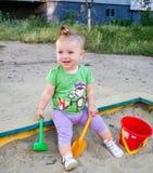 一点美好的女婴儿童游戏用桶提,倾斜和在微笑和显示它的牙的沙盒沙子的铁锹 免版税库存照片