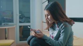 一点聊天青少年的女孩在社会媒介信使写一则消息 儿童技术和通信概念 股票录像