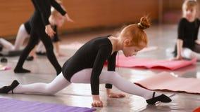 一点舒展和做锻炼的红发女孩芭蕾舞女演员在芭蕾学校 股票视频