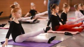 一点舒展和做锻炼的红发女孩芭蕾舞女演员在芭蕾学校 影视素材