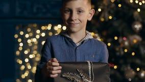 一点蓝色衬衣藏品圣诞礼物的逗人喜爱的男孩在手上 股票录像