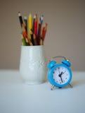 一点蓝色闹钟和一块玻璃与色的铅笔在ta 免版税库存图片