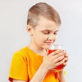 一点被切开的男孩喝新鲜的红色柠檬水 库存照片