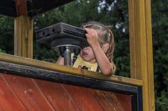 一点迷人的女孩通过在操场的玩具双筒望远镜看 库存照片