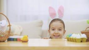 一点逗人喜爱和可爱的女孩恳切地微笑着 女孩挥动与手她小的舱内甲板  概念复活节假日 股票录像