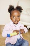 一点逗人喜爱甜非裔美国人女孩使用满意对玩具在家,生活方式儿童概念 库存照片