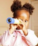 一点逗人喜爱甜非裔美国人女孩使用满意对玩具在家,生活方式儿童概念 免版税库存照片