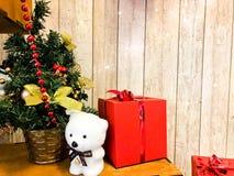 一点逗人喜爱的北极熊在新年的典雅的美丽的圣诞树下 新年的假日装饰和礼物红色箱子 库存图片