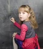 一点逗人喜爱的女孩文字画象在黑板的 免版税库存图片