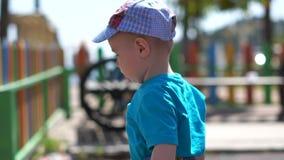 一点逗人喜爱的男孩在有五颜六色的木篱芭的,慢动作操场走 股票视频