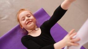 一点逗人喜爱的红发女孩芭蕾舞女演员在小组的背景的芭蕾学校执行伸展运动  股票录像