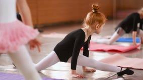 一点逗人喜爱的红发女孩芭蕾舞女演员在小组的背景的芭蕾学校执行伸展运动  股票视频