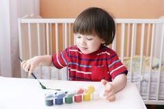 一点2年有刷子和树胶水彩画颜料油漆的男孩在家 免版税库存照片