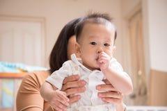 一点Asain男婴与拇指手指的7个月在嘴 免版税库存图片