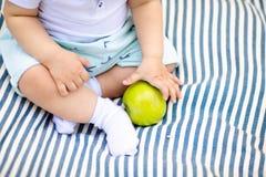 一点baby& x27;拿着黄色梨的s手指 库存照片