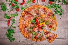 一热的薄饼margherita用肉、乳酪和香料在木背景 在一张灰色桌上的很多菜 免版税库存照片