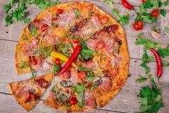 一热的薄饼margherita用肉、乳酪和香料在木背景 在一张灰色桌上的很多菜 免版税库存图片