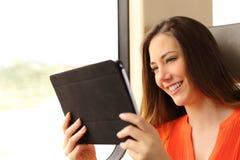 读一片剂或ebook在火车的乘客妇女 库存照片