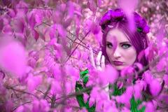 一片紫色叶子的一个美丽和美妙的女孩与红色花圈 免版税库存图片