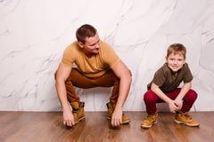 一现代年轻人和一个八岁的快乐的男孩橙色鞋子的 E 免版税图库摄影