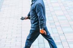 一男性擦净人在他的手上步行沿着向下在制服的街道并且拿着一个垃圾袋 图库摄影