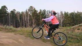 一白种人儿童乘驾在土公园骑自行车路轨道 女孩骑马黑色橙色周期在跑马场 孩子去做 股票视频