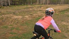 一白种人儿童乘驾在土公园骑自行车路轨道 女孩骑马黑色橙色周期在跑马场 孩子去做 股票录像