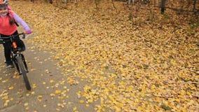 一白种人儿童乘驾在秋天公园骑自行车路 在森林孩子的女孩骑马黑橙色周期去做 影视素材