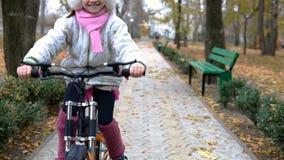 一白种人儿童乘驾在秋天公园骑自行车路 女孩骑马黑色橙色周期在公园 影视素材