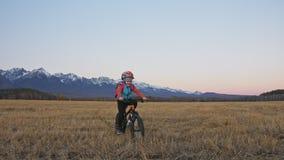 一白种人儿童乘驾在麦田骑自行车 在背景的女孩骑马黑色橙色周期美丽多雪 影视素材