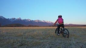 一白种人儿童乘驾在麦田骑自行车 在背景的女孩骑马黑色橙色周期美丽多雪 股票录像