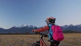 一白种人孩子走与在麦田的自行车 走在背景的女孩黑橙色周期美丽多雪 股票视频