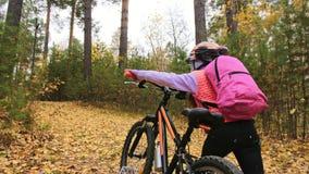 一白种人孩子走与自行车在秋天公园 走在森林孩子的女孩黑橙色周期去做 股票视频