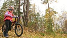一白种人孩子走与自行车在秋天公园 走在森林孩子的女孩黑橙色周期去做 股票录像