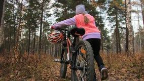 一白种人孩子走与自行车在秋天公园 走在森林孩子的女孩黑橙色周期去做 影视素材