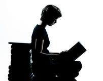 一白种人年轻少年剪影女孩读书 免版税库存图片