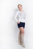 一白色女衬衫,蓝色短裤和高起动摆在的美丽的年轻金发碧眼的女人 库存图片