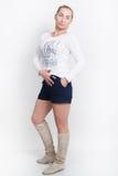 一白色女衬衫,蓝色短裤和高起动摆在的美丽的年轻金发碧眼的女人 图库摄影