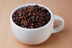 一白色杯有很多咖啡豆 免版税库存图片
