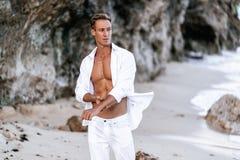 一白色衬衫的性感的肌肉人以胸部赤裸基于海滩,在背景的海浪 免版税库存照片