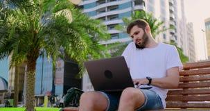 一白色T恤的一个人有膝上型计算机的谈话在电话在长凳的夏天 股票录像