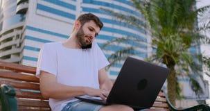 一白色T恤的一个人有膝上型计算机的谈话在电话在长凳的夏天 影视素材