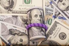 一百元钞票卷起与rubberband 免版税库存照片