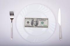 一百元钞票在白色板材说谎 免版税库存照片