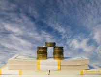 一百元钞票堆硬币和堆在组装的 免版税库存图片