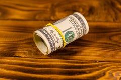 一百元钞票的卷与橡胶的在木桌上 免版税库存图片