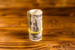 一百元钞票的卷与橡胶的在木桌上 免版税库存照片