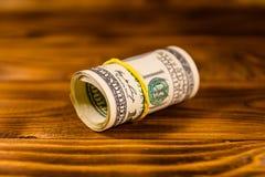 一百元钞票的卷与橡胶的在木桌上 库存图片