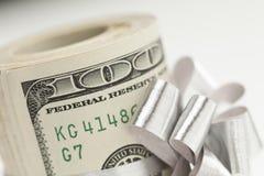 一百元钞票被栓的银色弓宏观卷在白色的 图库摄影